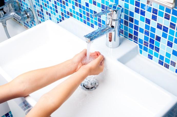 Girl washing her hands in bathroom sink